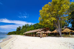 Tropical beach bungalow on ocean shore Stock Images