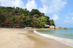 Tropical beach and bungalows on rocky hill Stock Images