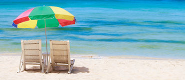 Tropical beach with chairs and umbrella Royalty Free Stock Photography