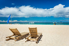 Tropical beach with chaise longues Royalty Free Stock Photos
