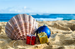 Tropical beach Christmas and New Year background. Merry Christmas and Happy New Year background with Seashell, gift and balls on the tropical beach near ocean in Stock Photos