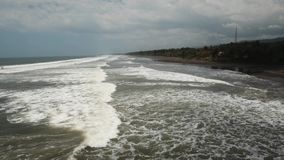 Beach, stormy weather, waves. Bali, Indonesia. Tropical beach at cloudy weather. Aerial view of big waves on the beach with volcanic black sand in windy weather stock footage