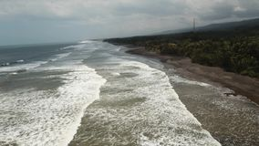 Beach, stormy weather, waves. Bali, Indonesia. Tropical beach at cloudy weather. Aerial view of big waves on the beach with volcanic black sand in windy weather stock video
