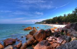 Tropical beach and coastline. A high definition view of a tropical Malaysian beach with a rocky coastline in the foreground Royalty Free Stock Photos