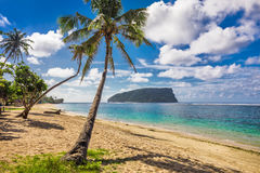 Tropical beach with a coconut palm trees and a beach fales, Samo. A Islands Stock Image