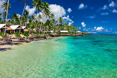 Tropical beach with with coconut palm trees and villas on Samoa Stock Images