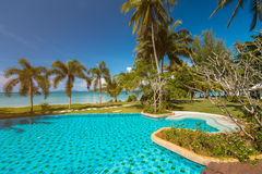 Tropical beach with coconut palms and swimming pool Stock Photography