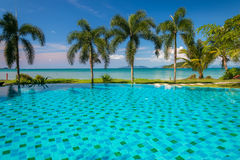 Tropical beach with coconut palms and swimming pool Royalty Free Stock Photo