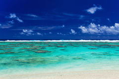 Tropical beach with coral reef and surf waves on Cook Islands Royalty Free Stock Photography