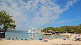 Tropical beach with cruise ship in distance. LABADEE, HAITI - APRIL 16, 2017: Tropical beach with Royal Caribbean cruise ship Navigator of the Seas docked at the stock video