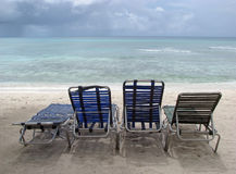 Tropical beach and deck chairs Stock Images