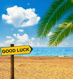 Tropical beach and direction board saying GOOD LUCK
