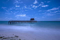 Tropical beach and dock at night stock image