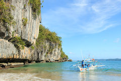 Tropical beach in El Nido, Palawan, with a boat man on a tipical Philippinos boat Royalty Free Stock Photos