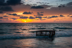 Tropical Beach with Empty Cage in the Sea at Sunset Royalty Free Stock Images