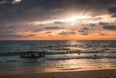 Tropical Beach with Empty Cage in the Sea at Sunset Royalty Free Stock Photo