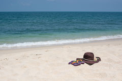 Tropical beach getaway. Straw hat and sandal on sandy beach Royalty Free Stock Photography