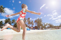 Tropical beach with girl running on foreground Royalty Free Stock Photography
