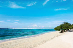 Tropical beach and green trees with blue sky. Landscape of tropical beach with blue ocean,white sand,blue sky and green trees Stock Image