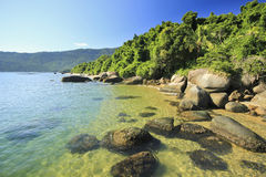Tropical beach with green water, stones on shore and bottom Stock Photo