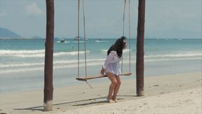 Young Beautiful Happy woman enjoying on a swing on the beach against the ocean background. stock footage