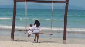 Young brunette girl swings on a beach swing with her son. Have fun on summer vacation. stock video footage