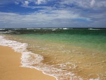 Tropical beach, Hawaii. Clear tropical ocean laps the shoreline during the quiet north shore summer Royalty Free Stock Photo