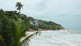 Tropical beach with heavy waving palm trees in a storm in front of a raving sea. 3840x2160 stock footage