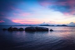 Tropical beach holidays landscape with calm turquoise sea and big round stones and rocks in sea during dramatic sunset in purple c. Tropical beach holidays Stock Images