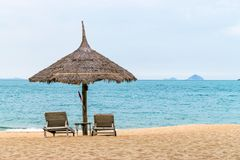 Tropical beach with hut and chairs near ocean royalty free stock photo