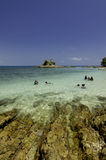 Tropical beach at Kapas Island, Malaysia. Wet Rock and crystal clear sea water with blue sky background Stock Image