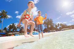 Tropical beach with kids splashing on foreground Royalty Free Stock Photo