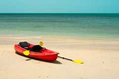 Tropical beach landscape with red canoe boat Royalty Free Stock Photos