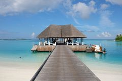Tropical beach landscape with wooden bridge and house on the water in Maldive island resort royalty free stock image