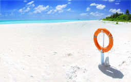 Tropical beach and lifebuoy panorama. Panoramic landscape of a beautiful tropical beach with orange lifebuoy in the foreground Stock Image