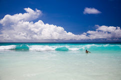 Tropical beach, man enjoy turquoise waves of ocean. Seychelles, Indian Ocean, beautiful greenish waves under curly clouds Stock Image