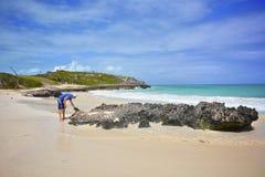 Tropical beach. A man examines the black rock on a sandy beach Stock Photos