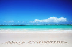 Tropical beach and merry christmas text. Clear tropical beach and merry christmas text in the sea sand Stock Photo