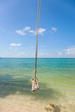 Tropical beach with Old  Swing Tied to tree Stock Photo