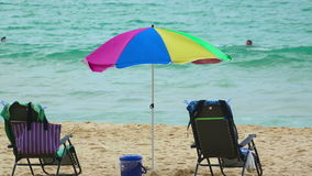 Tropical beach. Pair of chairs and an umbrella on the Karon beach, Phuket, Thailand stock video footage
