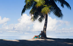 Tropical beach, palm tree with sitting blonde woman Royalty Free Stock Images