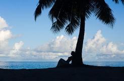 Tropical beach, palm tree with sitting woman, silhouette Royalty Free Stock Images