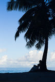Tropical beach, palm tree with sitting woman, silhouette Stock Photography