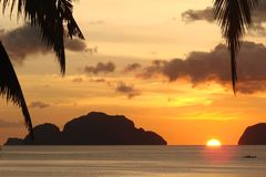 Tropical beach with palm trees at sunset, El Nido, Palawan island, the Philippines. Tropical beach with palm trees at sunset, El Nido, Palawan island in the Royalty Free Stock Photos