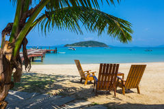 Tropical beach panorama with deckchairs, boats and palm tree Stock Photography