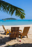 Tropical beach panorama with deckchairs, boats and palm tree Stock Photo