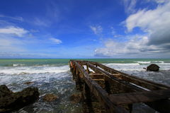 Tropical beach and pier. Scenic view of old wooden pier on beach with blue sky and cloudscape background, Ujung Kulon National Park, Java, Banten, Indonesia Royalty Free Stock Photo