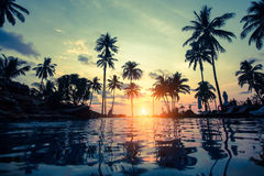 Tropical beach with pool and silhouetted palm trees during sunset. lagoon. Royalty Free Stock Photos