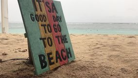 Tropical beach in a rainy day. Wooden plate with text it is a good day to go to the beach. Bali island. Tropical beach in a rainy day. Wooden plate with text it stock video footage