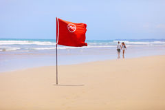 Tropical beach and a red flag. Do not swim! Stock Images